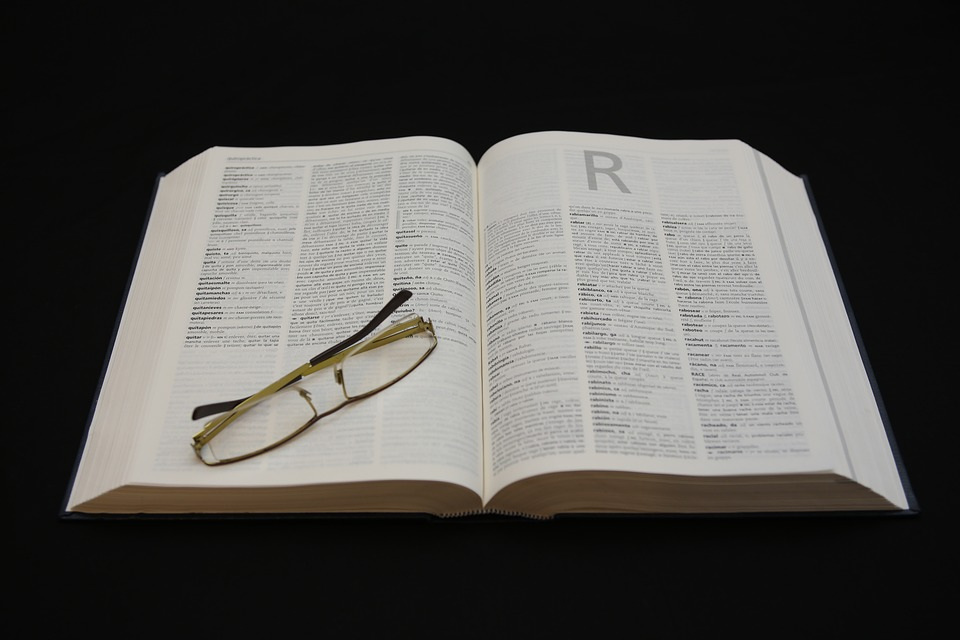 Open dictionary with spectacles resting on it